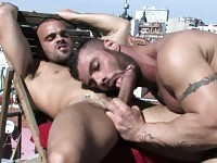 With the sun bathing their muscled bodies, two guys engage in anal sex