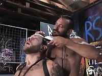 Two tattooed bears use ropes and clothespins in a gay BDSM encounter